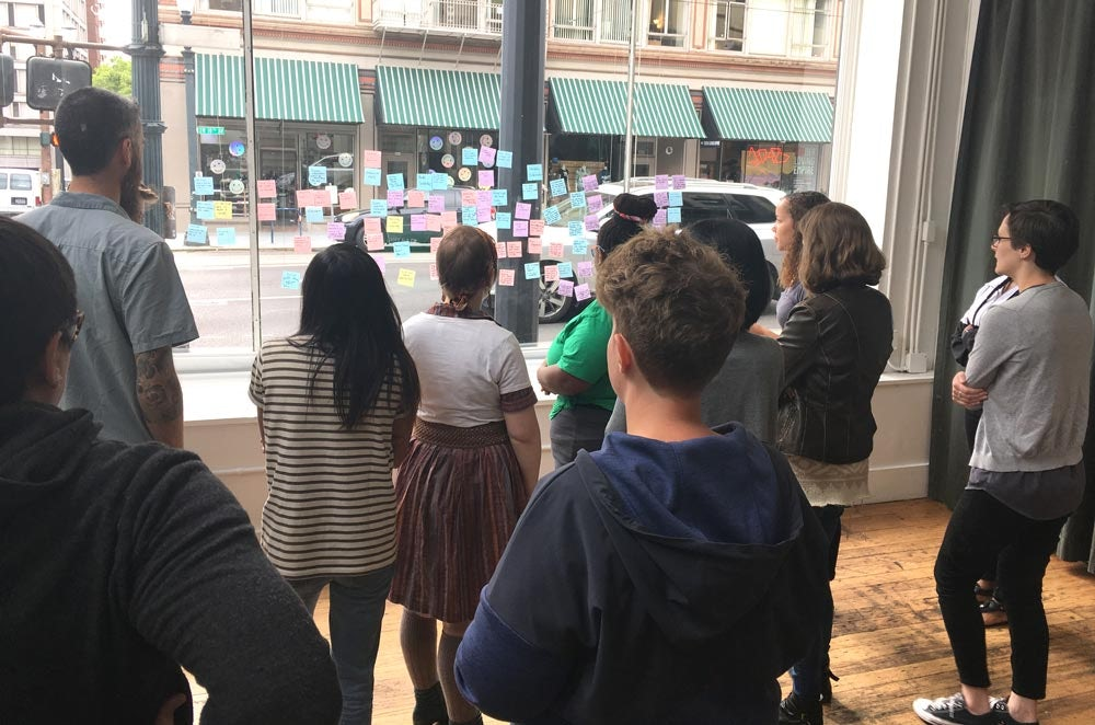 Team members sticking post-its on a window to gather ideas - one of three