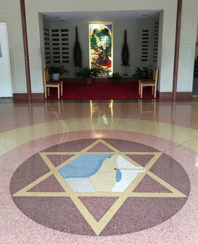 Detail of the floor of the Nineteenth Street Baptist Church. A gold Star of David contains a map of Israel with Jerusalem labeled. In the background is a stained glass window with an image of Jesus.