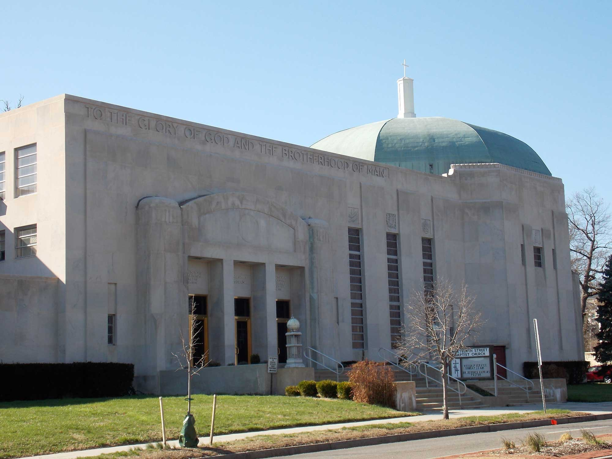 """The Nineteenth Street Baptist Church, a rectangular building made of grey limestone with a multi-sided rounded green dome on the right. An inscription reads """"To the glory of God and the brotherhood of man."""
